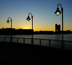Baltimore Inner Harbor Sunset (` Toshio ') Tags: city light sunset sun cold building water lamp silhouette harbor glow cityscape silhouettes maryland rail baltimore lamppost innerharbor toshio x100 fujix100
