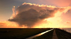 Bright sun behind the cumulonimbus on the dyke of Marken (Bn) Tags: travel pink blue houses light sea sky orange sun lighthouse haven holland history mill tourism monument water windmill dutch birds yellow clouds yard island fly flying geese wooden topf50 skies village bright flood wind stretch goose ganzen unesco round vista fields nes curve dyke dijk peninsula topf100 birdwatching rainfall dike hamlet marken authentic darkclouds ijsselmeer vastness waterland noord cumulonimbus zuiderzee 1857 terp werf vformation markermeer 100faves 50faves gouwzee gouwsea grotewerf moenis zereiderpad