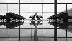 imperfect symmetry (Jon Downs) Tags: barcelona windows bw woman white black reflection art window monochrome digital canon downs photography grey mono photo airport spain chair jon flickr artist photographer floor chairs image seat gray picture pic powershot reflect tiles photograph seats departure g11 jondowns