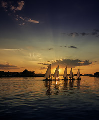 Sailing off into the sunset (Todd (Whitby61)) Tags: summer ontario canada clouds reflections pier waves harbour 5 sails silhouettes sailors july whitby backlit colourful sailboats lakeontario sunrays goldenhour dinghy breakwater sunfun godrays followtheleader