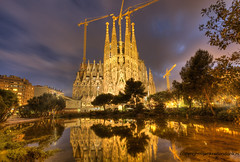 Under construction (Jan Kranendonk) Tags: blue trees sky reflection building art church water familia architecture night facade lights evening pond spain construction europe catholic cathedral dusk religion ngc sunny landmark illuminated cranes spanish gaudi sagrada lighted