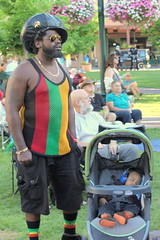 A kindness (ScribeGirl) Tags: plaza baby man newmexico santafe hat stroller headphones kindness fatherhood rasta hearing 65 113picturesin2013