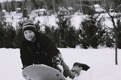 having some fun in winter (Anamaria Brigitte) Tags: winter boy bw white snow black smile yard fun kid moments child play time happiness glad laugh snowboard capture