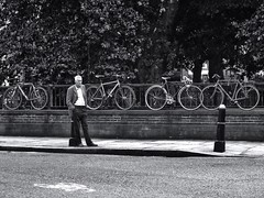 One Man, Five Bikes (Doug's Lumix) Tags: street bw man london lumix waiting candid bikes panasonic bicycles smithfield uploaded:by=flickrmobile flickriosapp:filter=nofilter