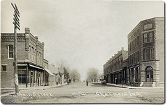 Main Street and post office, Chalmers, Indiana (Hoosier Recollections) Tags: houses horses people signs man men history cars boys kids buildings walking advertising children awning clothing cafe workmen mail postoffice hats restaurants streetscene transportation shops pedestrians storefronts waterpump residential automobiles banks businesses wagons barbers whitecounty realphoto hoosierrecollections