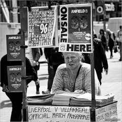 On sale here (John Riper) Tags: street uk family england bw woman white black cup monochrome liverpool canon john square photography mono football official zwartwit candid stall semi final l match greatest fc uefa 96 programme anfield 6d 24105 villarreal straatfotografie youneverwalkalone riper johnriper