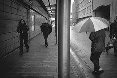 After the rain (der_Unsichtbare74) Tags: street people woman man cold rain umbrella walking blackwhite fuji rainyday streetphotography x100 centralperspective steelcolumn stphotographia fujix100