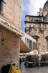 At the Poco Loco, Dubrovnik (wamcclung) Tags: window sign yellow architecture umbrella awning cafe architecturaldetail croatia dome lettering baroque dubrovnik pediment caffe cornice baroquechurch