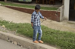 boy with a stick (Pejasar) Tags: boy child stick pocket hand balance branch curb grass brick play