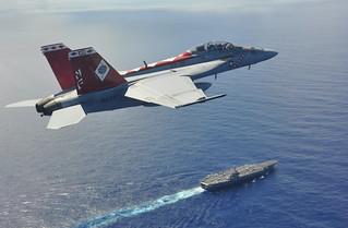 F/A-18F flies above USS George Washington in Philippine Sea.