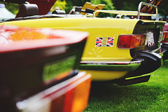 Yellow TR6 revisited (Eric Flexyourhead (shoulder injury, slow)) Tags: blue red white canada detail english car yellow vancouver zeiss sticker bc bokeh britishcolumbia flag triumph british motor unionjack tr6 fragment shallowdepthoffield 2016 allbritishfieldmeet vandusenbotanicalgarden triumphtr6 abfm 55mmf18 sonyalphaa7 zeisssonnartfe55mmf18za