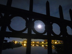 full moon through the fence, Druid Hill Park (Zombie37) Tags: park city blue summer urban moon lake black night reflections circle outside gold lights glow view outdoor framed circles baltimore reservoir fullmoon solstice round handheld moonlight inside strawberrymoon druidhillpark encircled