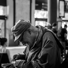 Enigma (Go-tea) Tags: street old city light portrait people urban bw sun white man black smile hat station train canon bag eos glasses hall newspaper blackwhite alone coat indoor wired inside lonely passenger toulouse raincoat bnw poeple 100d