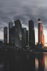 Skyscrapers in business district at evening in Moscow (thotran7989) Tags: city bridge sunset sky reflection building water modern clouds skyscraper river lights movement construction downtown commerce technology time top moscow space centre working corporation business company highrise land giants tall innovation facility embankment moscowcity lease cooperation eveing offcies