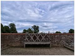 National Trust bench at Baddesley Clinton. (tetleyboy) Tags: wood blue sky cloud tree stone wall gardens bench landscape moss framed historical lichen stillife nationaltrust warwickshire facebook listedbuilding