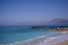 Old pier view at day (aleksey_kondratiev) Tags: turkey fethiye oludeniz mediterranean sea water blue wave waves seashore rocks sky pier rust mountain beach