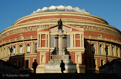 View of the Royal Albert Hall and memorial statue, South Kensington, London (Roberto Herrett) Tags: city uk travel blue england sky people urban music orange sun london english tourism sunshine k silhouette yellow horizontal by architecture buildings outside gold hall concert europe icons unitedkingdom britain decorative famous capital sightseeing victorian cities culture landmarks sunny grand places pd tourist symmetry architectural historic whole u dome pedestrians historical symmetrical classical british ornate venue iconic figures sights complete attractions locations stockphoto exteriors lavish passers rherrettflk
