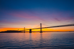 Sunset at Bay Bridge (Alex Zhu | Photography) Tags: california travel bridge blue sunset red sea sky usa beach water beautiful silhouette clouds america sunrise landscape outdoors dawn evening bay coast harbor san francisco peace pacific landmark calm commute silhouetted connection connect