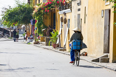 Old woman in conical hat is riding bicycle down the street of Hoi An Ancient Town (Evgeny Ermakov) Tags: life street old city travel blue red vacation urban woman flower green tourism hat bike bicycle asian daylight town ancient asia southeastasia vietnamese ride candid traditional transport culture sunny landmark scene tourist an unescoworldheritagesite unesco vietnam hoian riding exotic transportation delivery destination daytime local had southeast hoi conical touristic vietnamesehat conicalhat asianhat traditionalhat