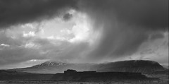 the friendly eye in a stormy sky (lunaryuna) Tags: sky bw panorama storm monochrome clouds season landscape blackwhite iceland spring lunaryuna cloudscape stormclouds mountainrange southeasticeland lightmood seasonalwonders stormadvancing