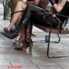 Heavy Metal Accessories (Halcon122) Tags: madrid street urban color leather club outside 50mm spain women punk downtown raw sitting boots candid streetphotography stranger heavymetal tattoos heels miniskirt dressed groupies plazadeespana epm2