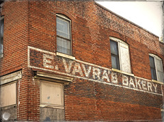 E. VAVRA'S BAKERY (FotoEdge) Tags: city winter shadow red signs sunshine sign corner vintage ads landscape geotagged ancient midwest downtown unitedstates painted bricks memories rusty stjoseph olympus gritty textures faded missouri bakery americana ghosts antiques roadside crusty relics rivertown omd winterlight crumbling relic ghostsign ghostsigns sentinels em1 streetside rustycrusty stjoe midwestern rustscape midwesttowns fotoedge nwmissouri wwwfotoedgecom midwesternsky bobtravaglione midwesternserenade microfourthirds porchpillars omdem1 olympusomdem1 hillsoftime copyright©2014 1204sycamore evavrasbakery