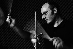 drummer (Dirk Philipp) Tags: portrait musician music motion blur drums glasses blackwhite sticks movement hands dynamic grain band motionblur drummer noise highiso xe1 xf35mmf14 jimsondrift