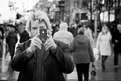 The Apple Of His Eye (Leanne Boulton) Tags: life road street city light portrait people urban blackandwhite bw sunlight white man black male eye apple monochrome face field smart fashion mobile modern composition contrast canon hair mono scotland living blackwhite aperture focus photographer technology phone bokeh pavement expression glasgow candid young cellphone cell style pedestrian scene sidewalk busy smartphone human blond shade portraiture area bandw filming depth facial zone shoppers stylish iphone vision:outdoor=0765 vision:sky=0808