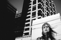Faces (matt.hagge) Tags: street camera city light shadow urban blackandwhite woman black tiara sexy girl monochrome beautiful face sex contrast digital 35mm hair photography daylight photo long day shadows natural emotion walk rangefinder billboard advertisement handheld ambient fujifilm crown daytime f2 fujinon f4 available harsh lightroom circlet 23mm apsc vsco x100t