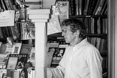 Where did I put my pencil ? (Go-tea) Tags: madrid street old boss portrait people urban bw white man black shop shirt pencil canon lost outside eos 50mm glasses blackwhite spain focus outdoor sunny books curly thinking curl es espagne bnw comunidaddemadrid 100d