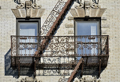 NYC fire escape. (astikhin) Tags: old city nyc windows red urban usa white house ny newyork color detail building brick home window glass vertical horizontal wall architecture stairs facade america outside fire us stair pattern escape exterior apartment unitedstates floor outdoor monogram manhattan steel details facades security safety ornament staircase fireescape housing service daytime ladder railing residence zigzag