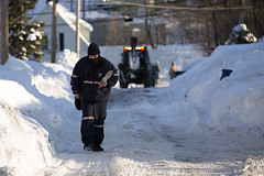 Braintree MA - A Postal Service letter carrier delivers mail on a snow covered Sheppard Ave as the National Guard works in the background removing snow from roadways. 2/13/15 (brianjdamico) Tags: snow usps postalservice mailman lettercarrier braintree unitedstatespostalservice braintreema masnow