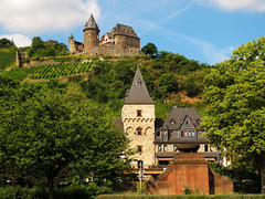 Stahleck Castle in Bacharach, Germany (Batikart) Tags: park city travel blue houses light shadow summer vacation sky sun holiday mountains color colour tree green tower castle nature weather wall architecture clouds forest canon germany landscape geotagged deutschland town europa europe peace sommer urlaub natur sightseeing wolken tranquility sunny medieval unescoworldheritagesite berge vineyards stadt recreation relaxation ursula turm landschaft burg reise sander bacharach mittelalter stahleck middlerhine rhinelandpalatinate mittelrhein 100faves 2013 200faves stahleckcastle viewonblack rhinegorge batikart canonpowershotg11