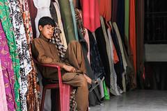 Fabric Seller (Menhaj Sharaf) Tags: boy afghanistan women fabric afghan seller herat shopkeeper 2014