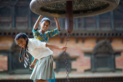 Nepali schoolgirls playing at a bell in hinduist temple, Bhaktapur, Nepal