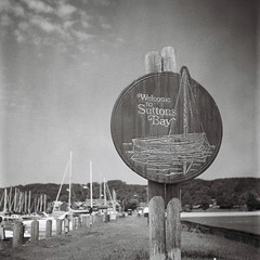 Safe Haven. (Rickenbackerglory.) Tags: blackandwhite film rolleiflex marina boat harbour michigan lakemichigan suttonsbay leelanaucounty