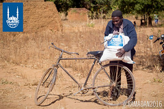 A man straps the Ramadan food pack distributed by Islamic Relief to his bike in Malawi.