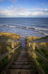 stairs to tide (thatgirlwiththekicks) Tags: blue ireland winter sky seascape beach grass clouds stairs wooden waves afternoon tide steps shoreline shore irishsea meath gormanston