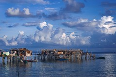 Fishing village (Syahrel Azha Hashim) Tags: ocean poverty travel light summer vacation holiday detail beautiful architecture clouds 50mm prime boat community nikon colorful southeastasia dof view getaway details horizon scenic lifestyle naturallight bluesky malaysia tropical handheld local shallow simple dramaticsky residential sabah basic unfortunate fishingvillage floatingvillage simplelife seagypsies woodenhouses housesonstilts d300s denawanisland syahrel