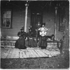 Men peeking out the window at four people on a porch (Meyersdale Public Library) Tags: people men dogs women hats 1900s 1890s 1880s porches photobox12 cookalbum