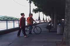 Walking the bike (dharder9475) Tags: 2000 35mm 4star bike england film london olympusom1 privpublic riverthames riverwalk streetphotography walking women