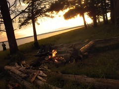 Sunset over the camp fire (Lost in Flickrama) Tags: wood camping sunset camp sky man black clouds trekking landscape fire gold site fireplace dusk hiking logs adventure yellowstone wyoming majestic