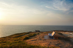 Stone seat at sunset in Sopelana coast (Mikel Martnez de Osaba) Tags: ocean travel blue sunset sea vacation sky cliff stone clouds bench relax chair view seat calm sit rest lonely recliner
