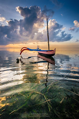 Typical wing boat of Sanur Beach Bali 2 (Vertical) (Sukarnjanaprai) Tags: sea sky bali cloud seascape reflection beach water sunrise boat wing reflect getty typical gettyimages sanur