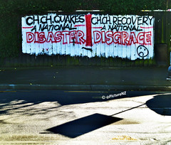 Disaster and Disgrace (Steve Taylor (Photography)) Tags: city shadow red newzealand christchurch white streetart black fence graffiti earthquake painted canterbury national disaster quake southisland cbd recovery disgrace sadface chch vision:text=0574 vision:outdoor=0882 vision:car=0833
