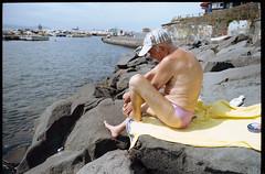 (Nail The Ingrowing Nail) (Robbie McIntosh) Tags: leicamp leica mp rangefinder streetphotography 35mm film pellicola analog analogue negative leicam elmarit analogico leicaelmarit28mmf28iii elmarit28mmf28iii dyi selfdeveloped filmisnotdead autaut candid tetenalcolortecc41 kodakcolorplus200 kodak beach tan seaside bathers strangers swimsuit speedo rocks ingrowingnail pedicure cap hat