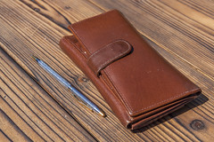 Brown wallet and ballpoint pen on wooden table (AudioClassic) Tags: old money leather horizontal pen table outdoors photography wallet object nopeople business pocket obsolete finance individuality ballpointpen wages browncolor woodmaterial