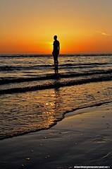Hiding the sun (snapnikonnick) Tags: sunset shadow man beach water liverpool waves seashore crosby