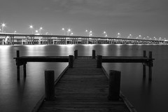 Highway Dock (jayRaz) Tags: wood longexposure bridge bw lake reflection water night lights dock highway streetlights over overpass supports lakerayhubbard gbt georgebushturnpike