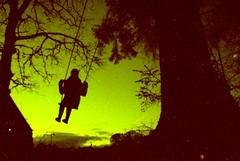 Cameron (MigKenzie Photos) Tags: camera uk portrait sky green film church silhouette pine dark toy person la scotland highlands lomo lomography crossprocessed sardina photos swing cameron analogue apc sutherland lomograph lairg lasardina migkenzie migkenziephotos